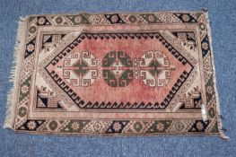 KARADAGH RUG, with row of three latch hook pattern medallions on a faded red field with spandrels,