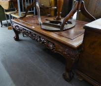 AN ORIENTAL MAHOGANY LARGE OBLONG COFFEE TABLE WITH DRAGON CARVED AND PIERCED APRON, ON FOUR MASK