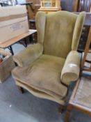 A GOOD QUALITY WING BACK ARMCHAIR, IN THE STYLE OF HOWARD AND SONS