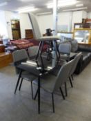 A MODERN STYLISH BLACK GLASS TOPPED DINING TABLE, RAISED ON TAPERING BLACK TV STYLE LEGS (140cm long