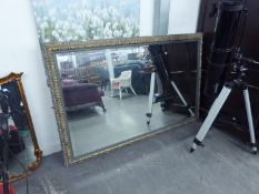 A LARGE OBLONG BEVELLED EDGE WALL MIRROR IN EBONISED GILT FRAME, 5?4? WIDE