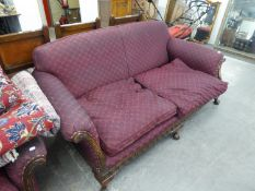 AN EDWARDIAN FEATHER STUFFED THREE SEATER SETTEE AND ARMCHAIR, UPHOLSTERED IN PURPLE FABRIC,
