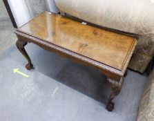 A CARVED AND FIGURED WALNUT OBLONG COFFEE TABLE WITH CARVED BORDER, ON FOUR ACANTHUS CARVED LEGS AND