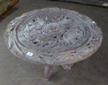 AN AFRICAN CARVED WOOD OCCASIONAL TABLE WITH REMOVABLE CIRCULAR TOP AND FOLDING THREE LEG BASE