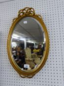 A SMALL OVAL BEVELLED EDGE WALL MIRROR IN GILT FRAME WITH RIBBON PEDIMENT
