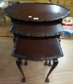 A NEST OF THREE MAHOGANY OVAL COFFEE TABLES, WITH MOULDED WAVY EDGES, ON SLENDER CABRIOLE LEGS, WITH