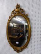 A GILT FRAMED OVAL WALL MIRROR (77cm high)