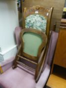 TWENTIETH CENTURY MAHOGANY STAINED AND CARVED FOLDING ROCKING CHAIR, with tapestry covered back
