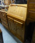A MODERN PINE BUREAU, WITH TWO DRAWERS OVER TWO CUPBOARDS