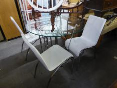 A DINING TABLE WITH CIRCULAR PLATE GLASS TOP ON THREE PAIRS OF BRIGHT METAL ?V? SHAPED SUPPORTS, THE
