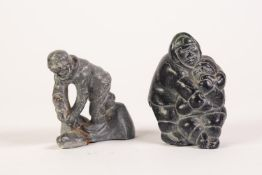 TWENTIETH CENTURY INIUT BLACK SOAPSTONE CARVING, mother feeding child a fish, inscribed to base with