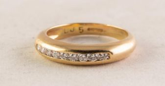 18ct GOLD AND DIAMOND RING channel set with a row of nine small round brilliant cut diamonds,