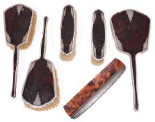 A George V Art Deco silver and tortoiseshell five piece dressing table set