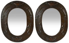 A pair of Arts and Crafts oval hammered copper wall mirrors