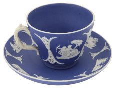A 19th century Wedgwood tea cup and saucer in white on dark blue dipped jasperware