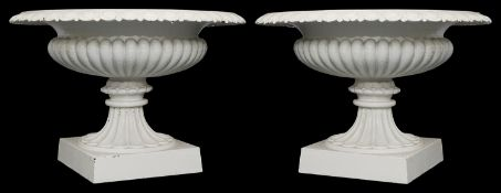 A pair of Victorian white painted cast iron garden urns
