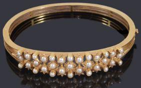 A decorative late Victorian gold seed pearl hinge bangle