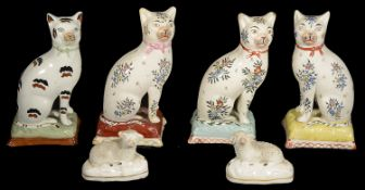 Four early 19th Century Staffordshire pottery cats and a pair of small recumbent sheep