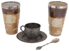 A late 19th c Indian Kutch silver teacup and saucer and two silver mounted Doulton stoneware beakers