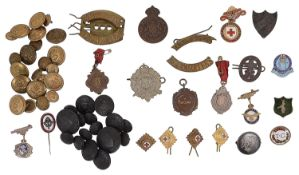 A collection of military buttons, fobs and cap badges