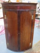 19th century oak and mahogany bow fronted wall mounted corner cupboard. Approx. 104cm H x 67cm W x