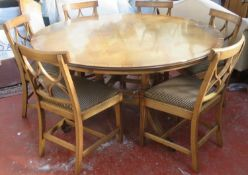 20th century inlaid oak circular topped dining table, on quadrafoil supports, with six curved leaves