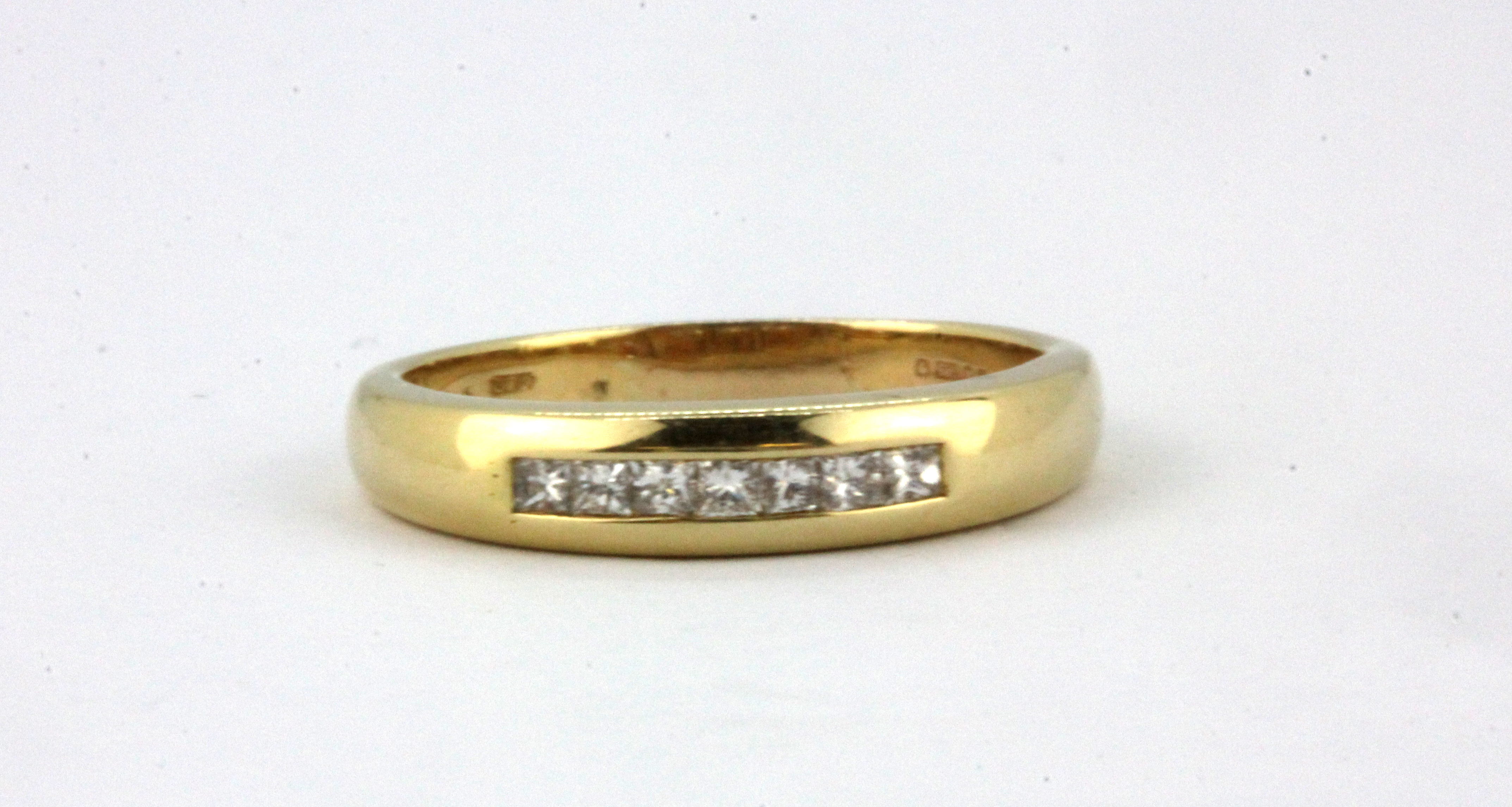 Lot 331 - A 14ct yellow gold (stamped 585) half eternity ring set with princess cut diamonds, (T).