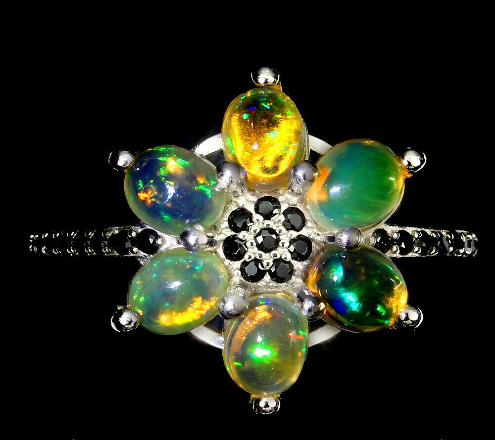 A 925 silver cluster ring set with cabochon cut opals and black spinels, (Q).