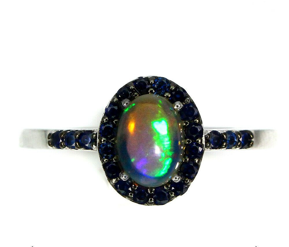 Lot 32 - A 925 silver cluster ring set with a cabochon cut opal and sapphires, (P).