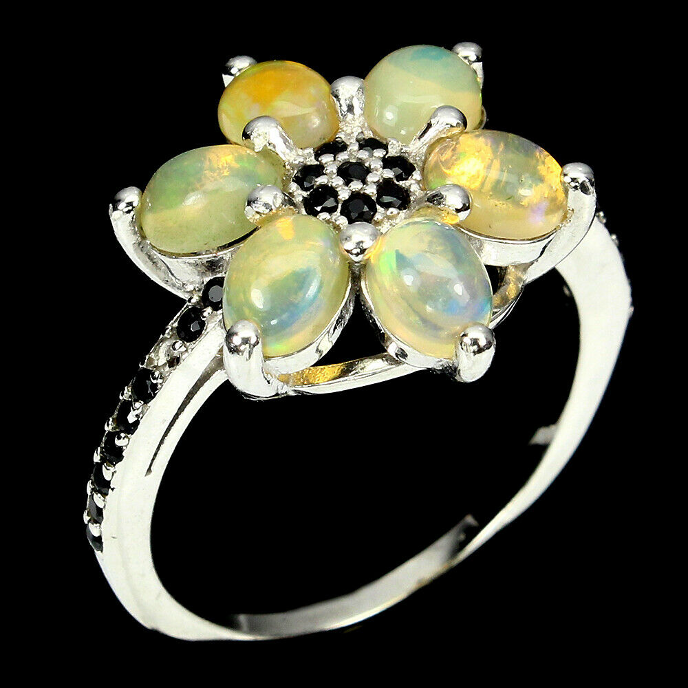 Lot 28 - A 925 silver cluster ring set with cabochon cut opals and black spinels, (Q).