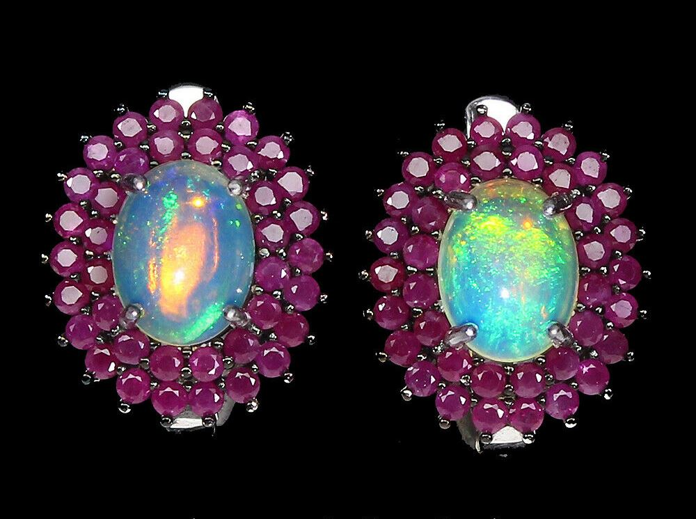 Lot 55 - A pair of 925 silver cluster earrings set with cabochon cut opals surrounded by two rows of