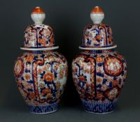A pair of 19th Century Japanese Imari porcelain jars and covers, H. 33cm.