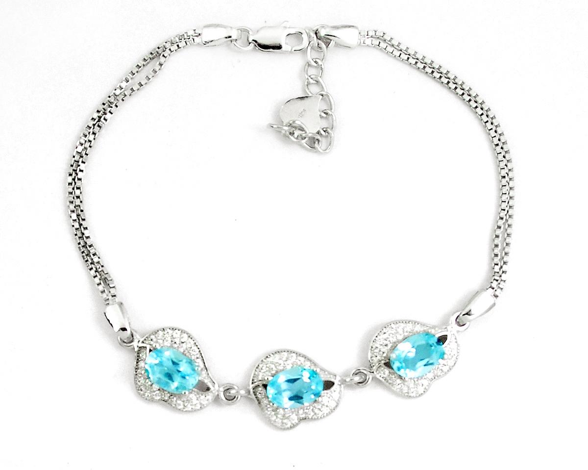 A 925 silver bracelet set with oval cut blue topaz and white stones, L. 17cm.