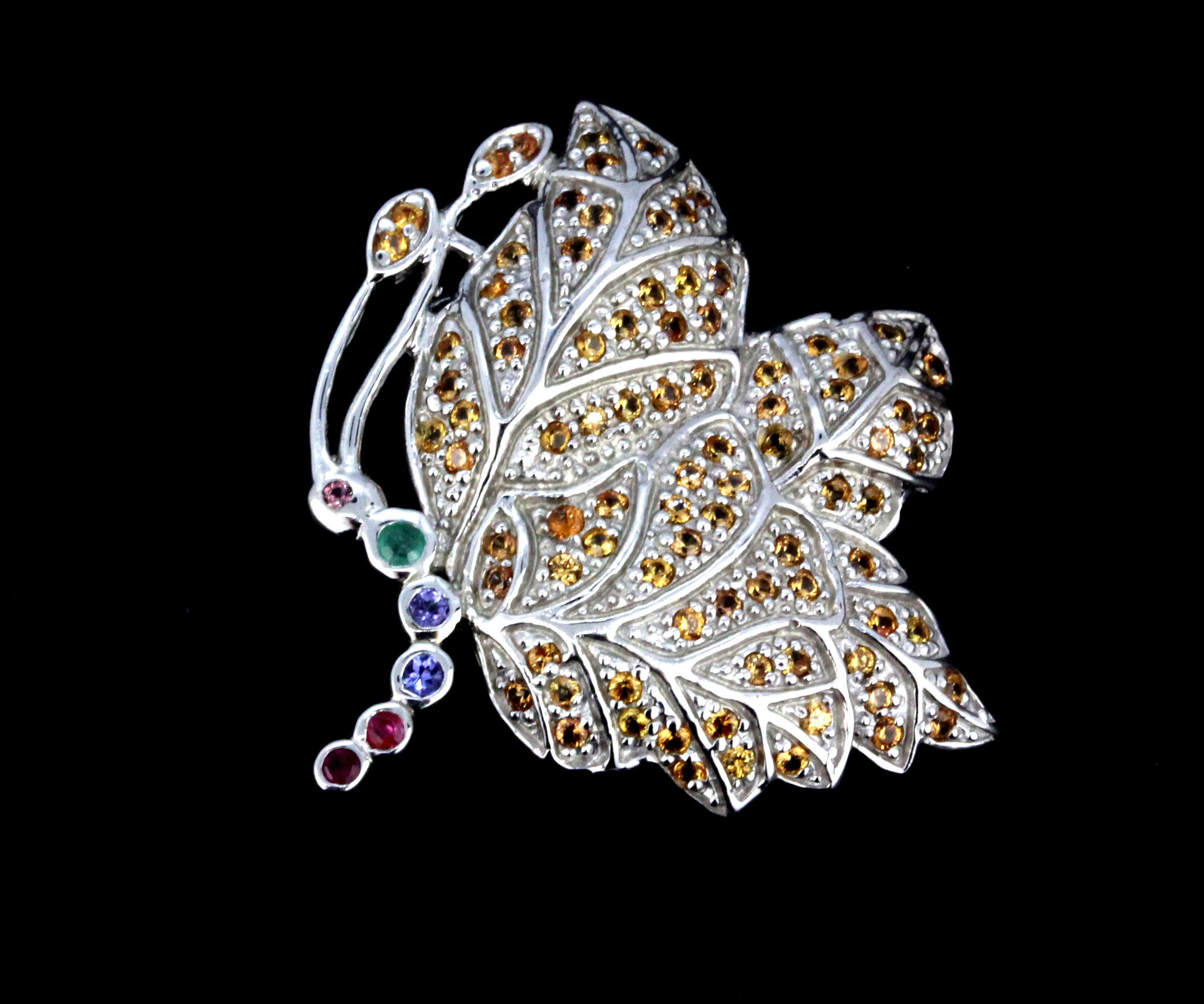 A 925 silver butterfly shaped brooch set with yellow sapphires, emerald, tanzanite and rubies, L.