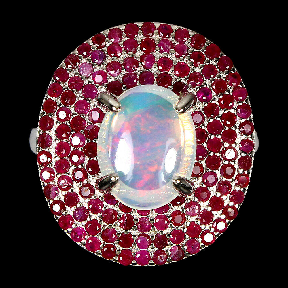A 925 silver cluster ring set with a cabochon cut opal and two rows of rubies, (N).