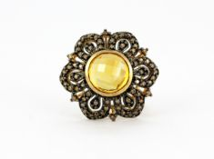 A 9ct yellow gold flower shaped ring set with a faceted cut citrine and brilliant cut fancy yellow