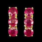 A pair of 925 silver gilt earrings set with round cut rubies, L. 1.1cm.