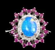 A 925 silver cluster ring set with a cabochon cut opal surrounded by rubies, (R.5).