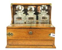An oak mirror backed and brass mounted Victorian tantalus with four cut glass decanters and silver