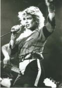 Kim Wilde signed 12 x 8 inch b/w photo singing on stage. Condition 8/10.