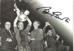 Football Bobby Charlton signed 6 x 4 inch b/w promo photo card holding up the European Cup.