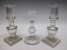 A pair of 19th century glass candlesticks and one 18th century facet candlestick