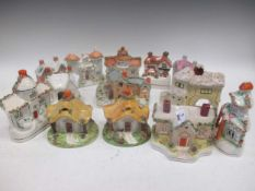 A collection of 13 Victorian and later Staffordshire pastille burner and money boxes in the form