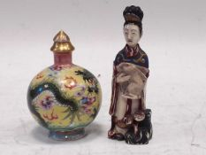 A Chinese carved and painted ivory snuff bottle, circa 1920, as a maiden holding a hare, ligzhi at