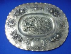 An early 20thC Continental silver oval Charger, in the Dutch style with repoussé decoration, the