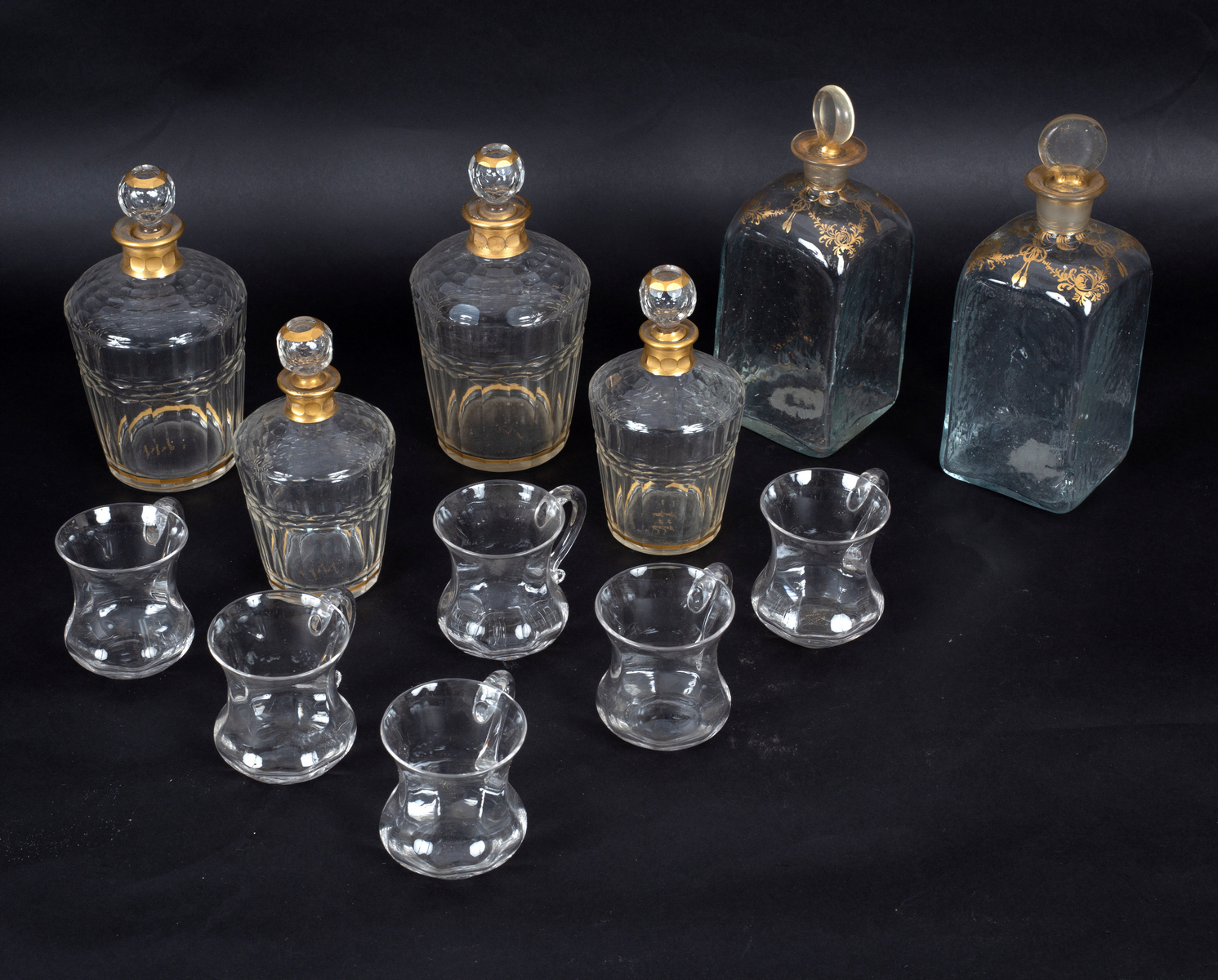 Lot 424 - A set of four decanters and stoppers with gilt collars, marked Daum Nancy, in two sizes,