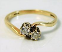 A 9ct gold crossover ring set with 0.15ct diamonds