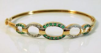A 9ct gold bangle set with diamonds & emeralds 6.5