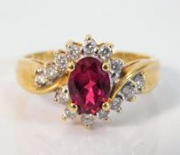 An 18ct gold ring set with 0.25ct diamond & red st