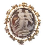 Unmarked yellow metal shell cameo brooch, relief-carved as Cupid and Psyche, with glazed reverse,